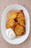 Potato pancakes with sour cream on a plate Royalty Free Stock Photos