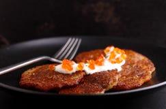 Potato pancakes with sour cream and red caviar Stock Photos