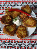 Potato pancakes with sour cream on a traditional ukrainian towel Stock Photo