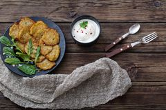 Potato pancakes with sour cream. On wooden table royalty free stock image