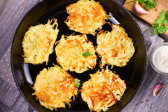 Potato Pancakes. Vegetable fritters. Latkes in frying pan. Stock Photos