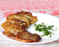 Potato pancakes on a white plate with sour cream and garlic sauc Royalty Free Stock Photos