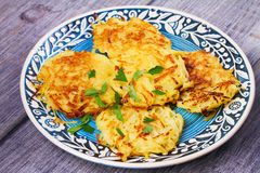 Potato Pancakes With Yogurt Sauce. Vegetable fritters. Latkes on blue plate. Stock Image