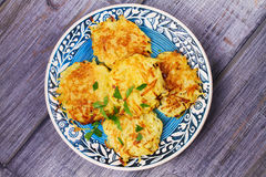 Potato Pancakes With Yogurt Sauce. Vegetable fritters. Latkes on blue plate. Royalty Free Stock Images