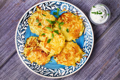 Potato Pancakes With Yogurt Sauce. Vegetable fritters. Latkes on blue plate. Royalty Free Stock Photography