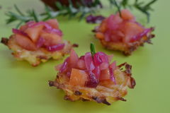 Potato and parsnip cakes with apple-onion-compote. Three potato cakes with rosemary in the background Stock Image