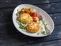 Potato patties and fresh tomato and celery salad on a light ceramic plate Stock Photo