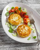 Potato patties and fresh tomato and celery salad on a light ceramic plate Stock Photography
