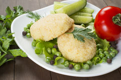 Potato patties with tomato, cucumber, green peas. Laid out on a white plate, decorated with greenery Stock Photos