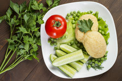 Potato patties with tomato, cucumber, green peas. Laid out on a white plate, decorated with greenery Stock Images