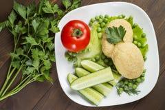 Potato patties with tomato, cucumber, green peas Stock Images
