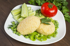 Potato patties with tomato, cucumber, green peas. Laid out on a white plate, decorated with greenery Royalty Free Stock Images