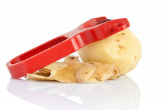 Potato peeler with peeled potato Stock Photos