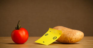 Potato with post-it note looking at tomato Stock Photo