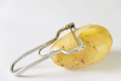 Potato with potatoe peeler Royalty Free Stock Photos