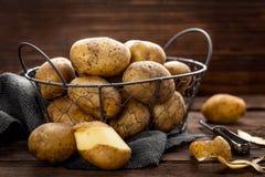 Potato. Raw yellow potato in basket on wooden table stock photo