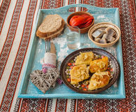 Potato rhombuses with fried onions, pickled herring and pepper o Stock Image