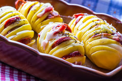 Potato.Roasts potatoes. Home cooking roasts potatoes. Baking pan full of baked potatoes stuffed with bacon sausage onions Royalty Free Stock Image