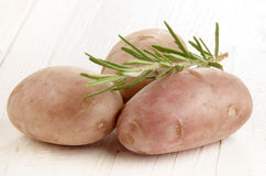 Potato and rosemary on white table Stock Photos