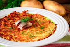 Potato rosti with dill and salted herring in plate on wooden table. Stock Photo