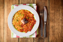 Potato rosti with dill and salted herring in plate on wooden table. Royalty Free Stock Images