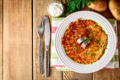 Potato rosti with dill and salted herring in plate on wooden table. Stock Photography