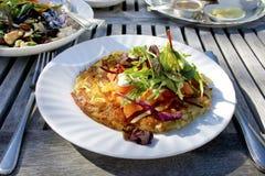 Potato rosti on a white plate. Potato rosti with smoked salmon and salad served alfresco Royalty Free Stock Photo