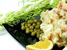 Potato salad. Close up of potato salad whit peas on black platter royalty free stock photo
