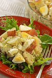 Potato Salad. With mayonnaise-based dressing; sitting on greens with fork on right Stock Photography