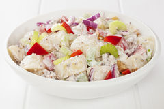 Potato Salad. With red capsicum, red onion, celery and walnuts in a honey mustard mayonnaise, on a white table royalty free stock photo