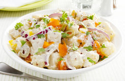 Potato Salad. A bowl of potato salad with creamy mustard dressing. Salad also includes orange and yellow peppers, red onions and stuffed olives royalty free stock image