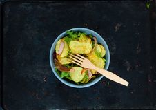Potato Salad with Bacon, richly seasoned with select spices in a blue bowl on vintage rusty metal background.Top view, copy space. Flat lay stock images