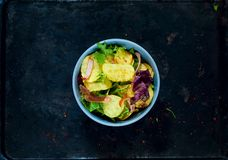 Potato Salad with Bacon, richly seasoned with select spices in a blue bowl on vintage rusty metal background.Top view,. Copy space, flat lay royalty free stock image