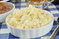 Potato salad. A bowl of potato salad on a picnic table with baked beans and beer stock images