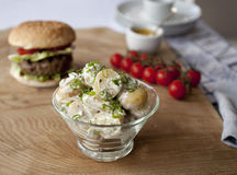 Potato salad with burger in background. Potato salad in a glass bowl, on wooden board with burger and cherry tomatoes and mustard in the background. Summery Royalty Free Stock Image