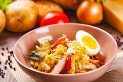 Potato salad with chicken and bacon in beige bowl. Close up royalty free stock image