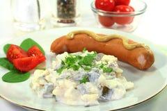 Potato salad with fresh herbs. Sausage and potato salad with fresh herbs stock photo