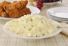 Potato salad and fried chicken. A bowl of potato salad, with fried chicken on a picnic table royalty free stock images