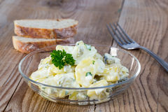 Potato salad in a glass bowl on wooden board Stock Photos