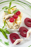 Potato salad with herring and beets. On a white plate Stock Images