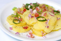 Potato salad from jacket potatoes. Salad from jacket potatoes, fortified with bacon and leek onions which are on a white plate royalty free stock image