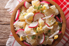 Potato salad with radish close-up in a bowl. horizontal top view. Potato salad with radish close-up in a bowl on the table. horizontal view from above Stock Photography