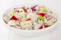 Potato Salad on white. Potato salad with red capsicum, red onion, celery and walnuts in a honey mustard mayonnaise, on a white table stock image