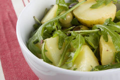 Potato Salad with Rucola. Lettuce in white bowl on red tablecloth stock image