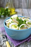 Potato salad with salted herring,marinated onion and eggs. Potato salad with salted herring,marinated onion and eggs in a blue bowl on rustic background Royalty Free Stock Photography