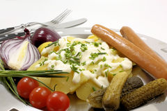 Potato salad with sausages. Onions and pickles stock photo