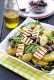 Potato salad with spinach, olives and grilled halloumi. Greek potato salad with spinach, olives and griled halloumi Stock Photos