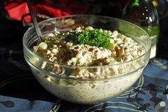 Potato salad on a table. A closeup of a bowl of potato salad, garnished with parsley and placed in a bowl on a table stock photo