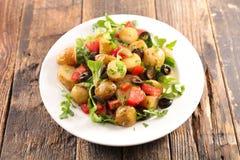Potato salad with tomato. On wood stock images