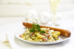 Potato salad with wiener sausage and parsley garnish on a white. Wooden table, typical german christmas dinner, copy space, selected focus stock image